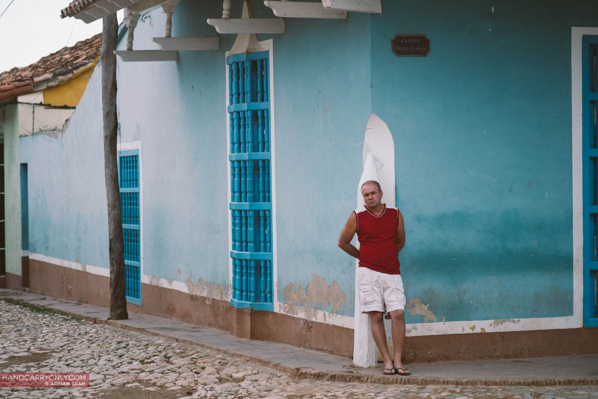 cuban man standing in front of blue wall
